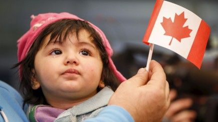 A Syrian refugee looks up as her father holds her and a Canadian flag as they arrive at Pearson Toronto International Airport in Mississauga, Ontario, December 18, 2015. REUTERS/Mark Blinch - RTX1ZBYD